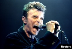 FILE - British Pop Star David Bowie screams into the microphone as he performs on stage during his concert in Vienna, Feb. 4, 1996.