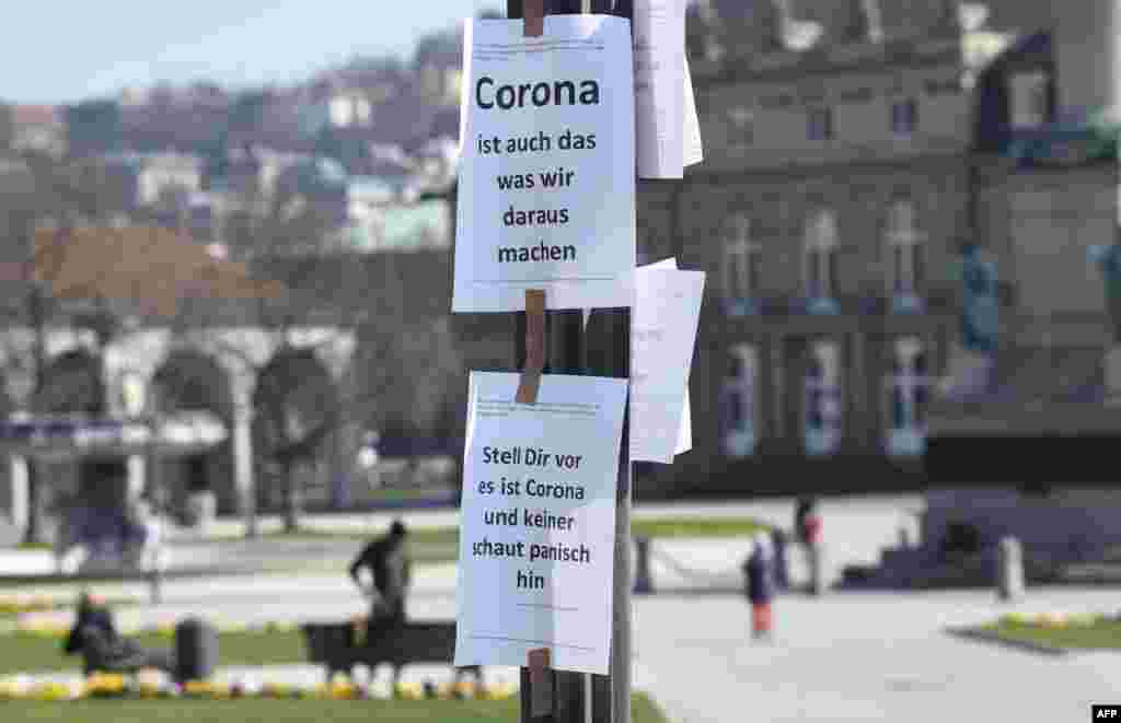 "Signs reading ""Corona is also what we do out of it"" (top) and ""Imagine this is Corona and nobody looks at it panickly"" are seen on a pole in Stuttgart, southern Germany."