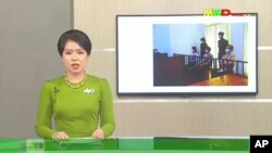 In this image from Myawaddy TV, a photograph of deposed Myanmar leader Aung San Suu Kyi's court appearance was shown during a report about her case is read by a news presenter Monday, May 24, 2021, in Naypyitaw, Myanmar. (Myawaddy TV via AP)