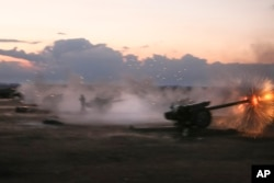 In this photo taken on Oct. 7, 2015, Syrian army howitzers fire near the village of Morek in Syria.