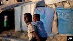 Seorang anak laki-laki menggendong adiknya ke sekolah, di sebuah tenda penampungan untuk korban gempa bumi 2010 di Port-au-Prince, Haiti (Foto: dok).