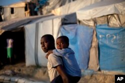 FILE - A boy carries his little brother to school, at a camp for people displaced by the 2010 earthquake, at what was once a golf club, in Port-au-Prince, Haiti.