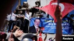 Para pendukung Presiden Erdogan mengangkat spanduk dengan foto Presiden Turki Tayyip Erdogan selama unjuk rasa pro-pemerintah (19/7). Istanbul, Turki (foto: REUTERS/Alkis Konstantinidis)