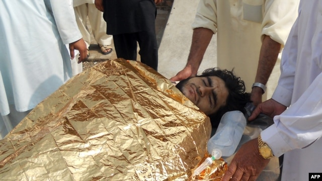 Pakistani men carry an injured bombing victim into a hospital in Kohat following an attack on the home of Maulvi Nabi Hanfi, Oct. 3, 2013.