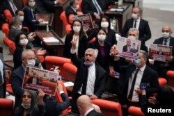រូបឯកសារ៖ លោក Omer Gergerlioglu សមាជិករដ្ឋសភាមកពីគណបក្ស Peoples' Democratic Party ដែលគាំទ្រជនជាតិឃឺដ និងសមាជិកសភាផ្សេងទៀត បង្ហាញការប្រឆាំងនឹងសេចក្តីសម្រេចរបស់រដ្ឋសភាដែលដកអភ័យឯកសិទ្ធិរបស់លោក នៅវិមានសភាតួកគី ក្នុងទីក្រុង Ankara ប្រទេសតួកគី កាលពីថ្ងៃទី ១៧ ខែមីនា ឆ្នាំ ២០២១។