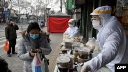 Karyawan restoran mengenakan pakaian pelindung saat berjualan di luar restoran mereka di Beijing, 20 Februari 2020.