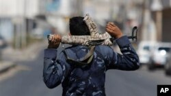 Policeman with cloth-covered weapon stands guard in Sanaa, Yemen, Feb. 23, 2014.