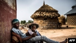 Le berger des Fulani, âgé de 30 ans, Isa Ibrahim utilise son téléphone tout en jouant avec son fils Suleima Isa, âgé de 4 ans, devant son domicile dans la réserve de Kachia Grazing, État de Kaduna, au Nigeria, le 16 avril 2019.