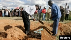 FILE: Relatives cover the grave of a cholera victim in Zimbabwe.