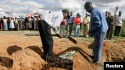 FILE: Relatives cover the grave of cholera victim Betty Mubata during her burial at Chitungwiza Unit L cemetery, 27km (17 miles ) south of the capital Harare, December 8, 2008. REUTERS/Philimon Bulawayo (ZIMBABWE) - RTR22E3J
