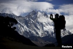 FILE - A tourist is silhouetted as he takes pictures of Mount Nuptse (C) as Mount Everest (L) is covered with clouds in Solukhumbu district, also known as the Everest region, Nov. 30, 2015.