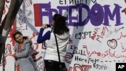 Anak-anak muda Mesir berfoto di depan dinding bermural di jalan menuju Alun-alun Tahrir di pusat kota Kairo, Mesir. (Foto: Dok)