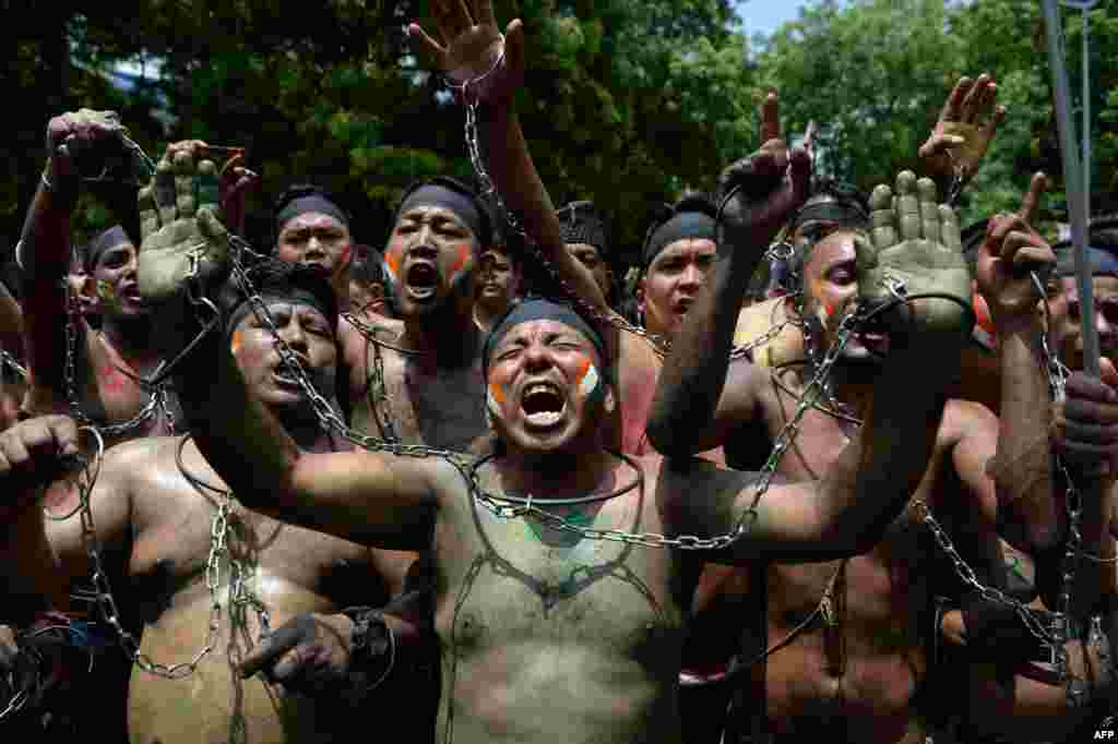 Indian supporters of Gorkhaland chant slogans tied with chains during a protest march in capital New Delhi.
