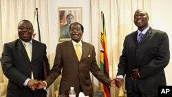 Robert Mugabe, ao centro, com primeiro-ministro Morgan Tsvangirai ,à esquerda, e Arthur Mutambara número dois do governo.