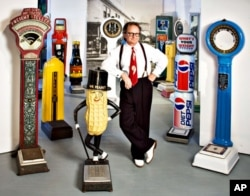 In his artist's studio, Christopher Steele strikes a rakish pose among his collection of vintage penny scales – some dispense fortunes and trinkets