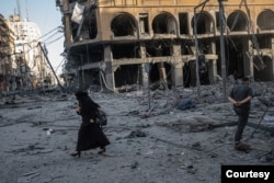 A woman walks past bombed-out buildings in Gaza, in this image captured by Fatima Shbair during the 11-day war in May 2021. Shbair risked her life to photograph scenes from the war. (Photo by Fatima Shbair/Courtesy of Getty Images)