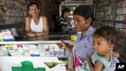 "This Aug. 26, 2009 photo shows a merchant in Pailin, Cambodia speaking with a woman as she holds her sick child at a drug store. Posters with message: ""Counterfeit medicine kills, while real medicine heals"" will be distributed to public hospitals, health"