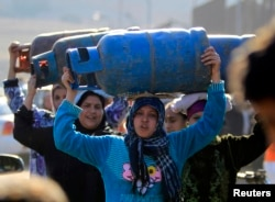Women carry gas cylinders to fill them at a distribution point in Cairo, Jan. 19, 2015.