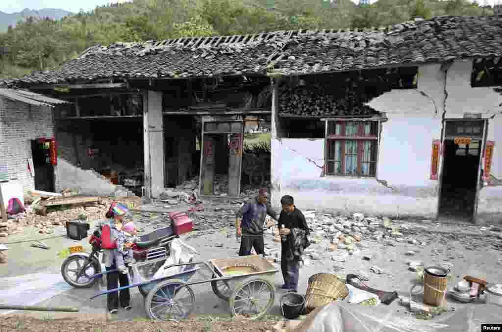 Người dân đứng bên ngoài một ngôi nhà bị hư hại sau khi xảy ra trận động đất mạnh 6,6 độ Richter, tại làng Long Môn, huyện Lô Sơn, Nhã Yên, tỉnh Tứ Xuyên, ngày 20 tháng 4, 2013.