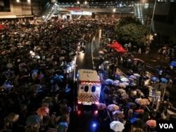 星期三凌晨,傾盆大雨中示威者有秩序地撐起雨傘,並讓出人道救援通道讓救護車通過。(美國之音湯惠芸攝)