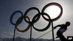FILE – A skier passes by the Olympic rings at the 2014 Winter Olympics, in Krasnaya Polyana, Russia, Feb. 20, 2014. The International Association of Athletics Federations postponed a final decision over Russia's eligibility for the 2016 Olympics until May.
