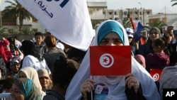 A supporter of the Islamic Ennahda party displays her national flag during a rally in Ben Arous, south of Tunis, October 21, 2011.