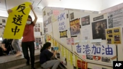 在台灣的香港學生為執行當地政府的指令從一面連儂牆上移走標語。 (2019年8月31日)