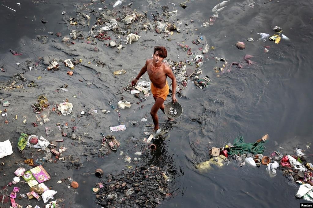 인도 뉴델리의 야무나강에서 한 남성이 쓰레기를 체에 거르고 있다.
