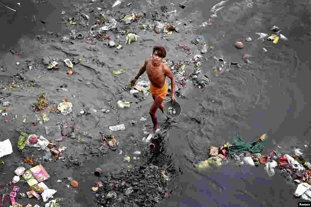 A man sifts through rubbish in the Yamuna river in Delhi, India.