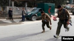 Afghan security forces run after a suicide car bomb attack in Jalalabad province, March 20, 2014.