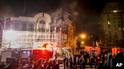 Smoke rises as Iranian protesters set fire to the Saudi Embassy in Tehran, Sunday, Jan. 3, 2016. Protesters upset over the execution of a Shi'ite cleric in Saudi Arabia set fires to the Saudi embassy in Tehran.