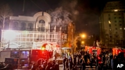 Smoke rises as Iranian protesters set fire to the Saudi embassy in Tehran, Jan. 3, 2016.