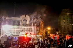 Smoke rises as Iranian protesters set fire to the Saudi embassy in Tehran, Jan. 3, 2016, to protest against the execution of a Shi'ite cleric by Saudi authorities.