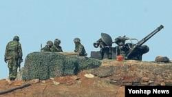 북한이 정전협정 백지화를 선언하고 위협 수위를 높이는 가운데, 13일 오전 한국 연평도 초소에서 해병대원들이 경계작전을 펼치고 있다.