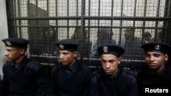 Des accusés dans un box lors d'un procés dans un tribunal du Caire, 26 février 2012.