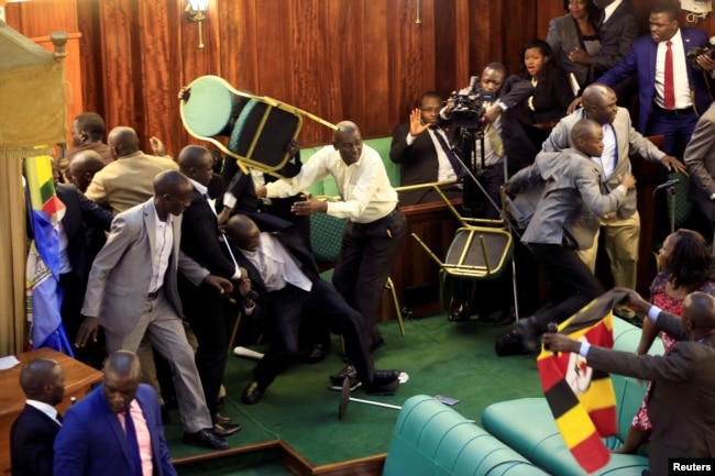 FILE - Ugandan opposition lawmakers fight with plain-clothes security personnel in the parliament while protesting a proposed age limit amendment to the constitution for the extension of the president's rule, in Kampala, Sept. 27, 2017.