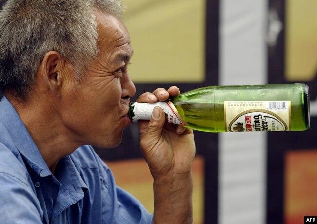 Seorang pekerja bangunan minum bir saat istirahat kerja di Beijing, China, 30 Juli 2004.
