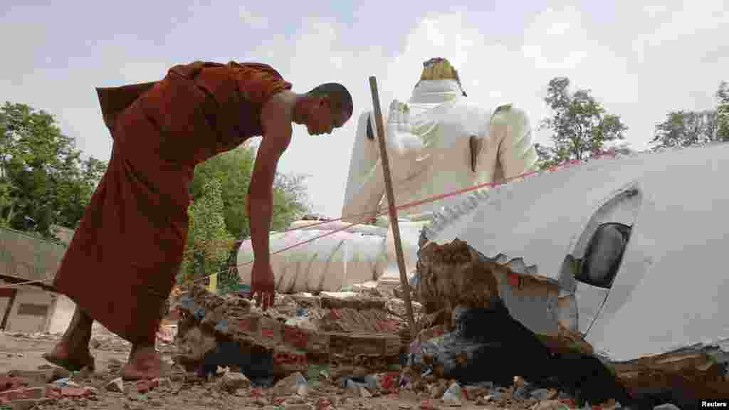 A Buddhist monk checks a statue of Buddha that was damaged by an earthquake at the Udomwaree temple in Chiang Rai, northern Thailand, May 6, 2014.