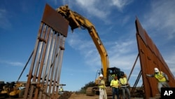 Construction crews install new border wall sections, Jan. 9, 2019, seen from Tijuana, Mexico. U.S. President Donald Trump walked out of his meeting with congressional leaders Wednesday as efforts to end the 19-day partial government shutdown fell into dee