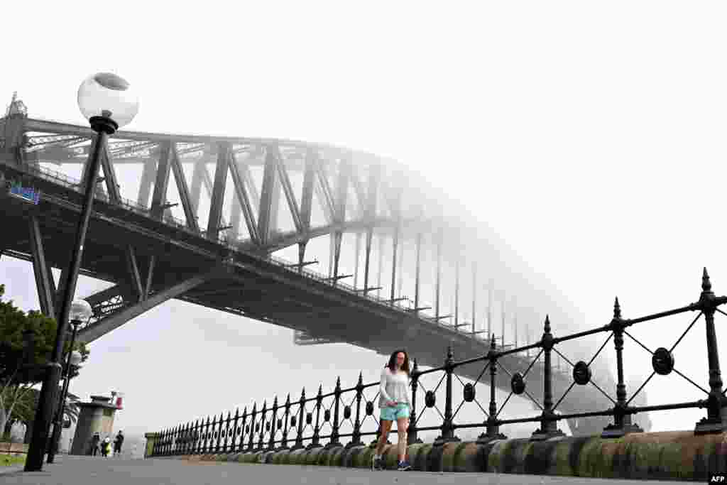 People walk under Australia's iconic landmark Harbour Bridge in Sydney, Australia, as heavy fog blankets the city.