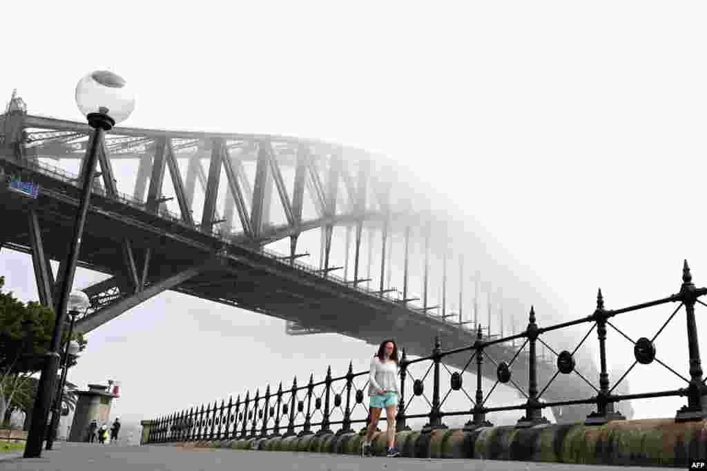 ប្រជាជនដើរកាត់ស្ពានអូស្រ្តាលី Harbour Bridge ក្នុងទីក្រុងស៊ីដនីខណដែលទីក្រុងនេះត្រូវបានគ្របដណ្តប់ដោយអាប់ក្រាស់។