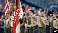 FILE - A color guard of Boy Scouts salute during the national anthem before a baseball game in Seattle, May 25, 2014.