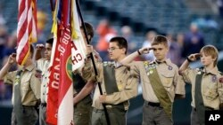 A color guard of Boy Scouts from the Chief Seattle Council salute during the national anthem before a baseball game between the Seattle Mariners and Houston Astros in Seattle, May 25, 2014.