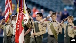 FILE - A color guard of Boy Scouts from the Chief Seattle Council salute during the national anthem before a baseball game between the Seattle Mariners and Houston Astros in Seattle, May 25, 2014.