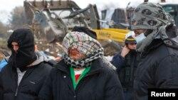 چند مهاجر ایرانی که لب های خود را در کاله دوخته اند.