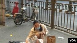 2020年6月14日,北京疫情再起。安徽进京创业的张女士业余时间在街头卖手机配件,因生意不好提前收摊。(美国之音叶兵拍摄)