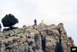 FILE - A Hezbollah fighter stands on a hill next to the group's yellow flag in the fields of Assal al-Ward, Syria, May 9, 2015.