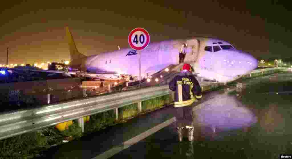 A firefighter stands in front of a cargo plane that exited the runway after sliding onto a local road in Orio al Serio, next to Milan, Italy, in this handout picture provided by Italy's Fire Fighters.
