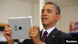 FILE - President Barack Obama holds up an Apple iPad during a visit to Buck Lodge Middle School in Adelphi, Maryland, Feb. 4, 2014.