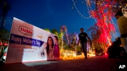A man walks on a footpath decorated with lights and billboard by workers capital development authorities to observe International Mother's Day celebration in Islamabad, Pakistan, May 7, 2016.